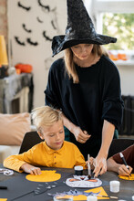 Young Teacher In Black Pullover And Witch Hat Pointing At Skull Picture Drawn By One Of Kids