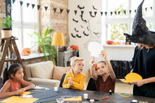 Little Girl Pointing At Halloween Paper Symbol While Showing It To Cute Boy By Table