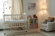 Interior of large cozy room of newborn baby with cradle, toys and furniture