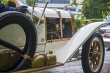 Close-up Of Elegant Refined White Gold Antique Retro Sport Renovated Car 1914 On Exhibition. Man Driving In Old Vintage Classic Automobile With Umbrella, Opened Motor, Wooden Wheels, Cool Horn