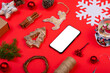 Leinwandbild Motiv Composition of smartphone with copy space and christmas decorations on red background