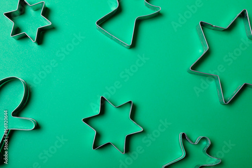 Composition of stars and angels ginger man cookie cutters on green background