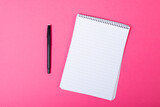 Composition of notebook with copy space and pen on pink background
