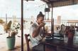 Mężczyzna, cyfrowy nomada pracujący z laptopem i telefonem przy stoliku w kawiarni, praca zdalna podczas podróży.