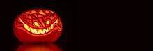 Illuminated Artistic Halloween Pumpkin On Black Panoramic Background. Halloween Web Banner