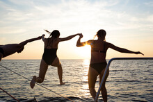 A Group Of Friends Jumping Into The Sea From A Yacht At Sunset