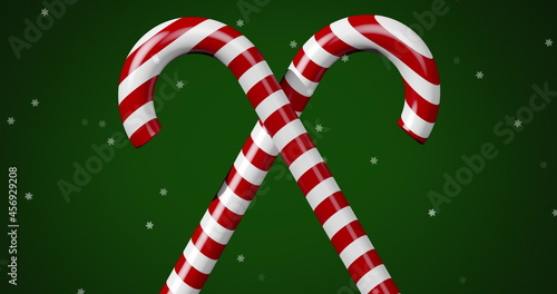 Digital image of multiple stars moving over two christmas candy cane against green background