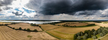 Aerial Panoramic Of The British Countryside With A Thunder Storm Rolling In. In The Distance You Can See A Cloud Burst And Rain Falling