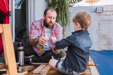 Father With Son Measuring Wooden Pieces With Tape
