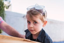 Dreamy Boy In Protective Glasses Against Wooden Stool