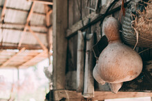 Dried Gourds And Utensils Hang Beside The Wooden Wall.