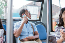 Male Asian Using Mobile Phone While Riding Public Bus Or Metro