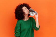 Portrait Of Greedy Woman With Afro Hairstyle Wearing Green Casual Style Sweater Holding And Smelling Fan Of Hundred Dollar Bills, Big Profit. Indoor Studio Shot Isolated On Orange Background.
