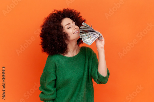 Fotografia Portrait of greedy woman with Afro hairstyle wearing green casual style sweater holding and smelling fan of hundred dollar bills, big profit