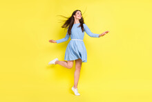 Photo Of Cute Pretty Young Woman Dressed Blue Clothes Dancing Looking Empty Space Smiling Isolated Yellow Color Background