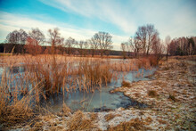View Of The Countryside And Frozen Winding Brook In The Evening At Sunset Light