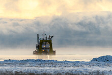 Vessel Engaged In Dredging. Dredger Working At Sea. Ship Excavating Material From A Water Environment. Strong Fog In Arctic Sea. Construction Marine Offshore Works. Dam Building, Crane, Barge, Dredger