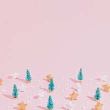 Creative Christmas Pattern Made Of Wooden Stars, Christmas Trees And Pearls On A Pink Backgorund With Copy Space. Minimal New Year Concept. Winter Inspiration.
