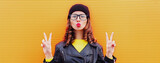 Portrait of beautiful young woman blowing her lips wearing a black leather jacket and hat, yellow sweater on an orange background
