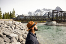 Man Standing On River Bank In Front Of Bridge And Mountain