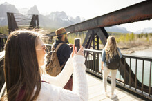 Friends Taking Photos Of View From Bridge