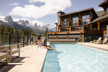 Couple Dipping Feet In Pool With Mountain View