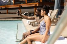 Couple Taking Selfie Sitting On Edge Of Pool