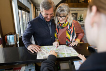 Receptionist Showing Map To Hotel Guests