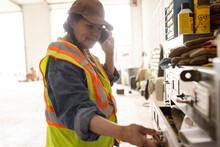 Female Mechanic Talking On Smart Phone In Barn