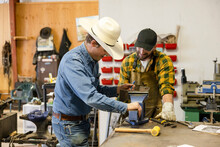 Male Bits And Spurs Makers Using Equipment In Workshop