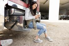 Teenage Girl Using Smart Phone At Semi Truck On Farm