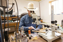 Male Farmer Working At Microscope