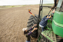 Farmer Mother Helping Son Climb Into Tractor On Farm