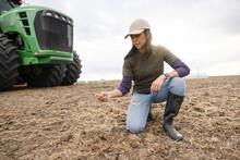Female Farmer Inspecting Soil On Rural Farm