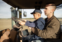 Father And Son Farmers Driving Tractor