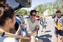 Mother Giving Baseball Bat To Daughter At Rear Of Vehicle