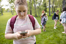 Close Up Of Student Texting On Phone In Park