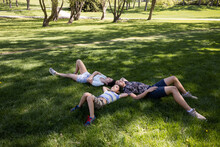 Siblings Laying Down On Grass In Park