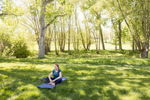 High Angle View Of Mature Woman Meditating In Park