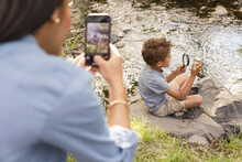 Boy Looking At Bottle With Magnifying Glass By River