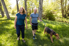Cheerful Mature Couple Taking Pet Dog For Walk In Park