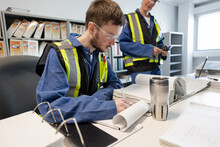 Mechanics Reviewing Paperwork In Maintenance Facility Office
