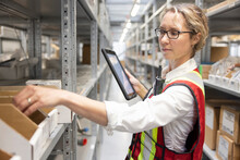 Female Supervisor With Digital Tablet In Parts Warehouse