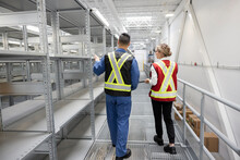 Workers In Reflective Vests Walking In Parts Warehouse