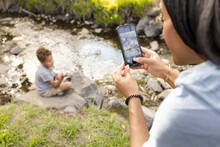 Close Up Of Mother Taking Photograph Of Son By River