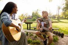 Cheerful Mother Teaching Son Play Guitar On Park Bench