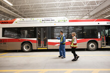 Engineers Inspecting Bus In Maintenance Facility