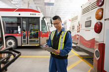 Male Worker With Clipboard In Bus Transit Garage