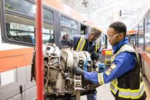 Male Mechanics Repairing Bus Engine In Maintenance Facility