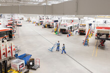 Workers With. Hand Truck In Large Bus Maintenance Facility